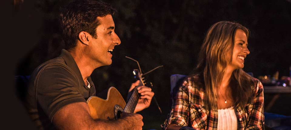 Couple playing guitar by campfire